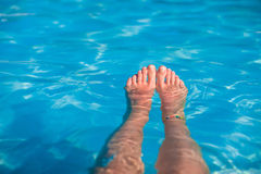 Close-up of female foot in the blue water Royalty Free Stock Photography