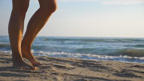 Close up of female foot stepping on the sand with sea waves at background. Beautiful woman walking on the coast barefoot