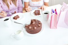 Close-up of female friends eating a chocolate cake Royalty Free Stock Image