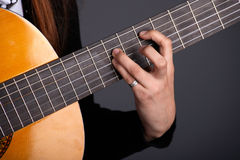 Close up of female guitarist hand playing guitar Royalty Free Stock Photography