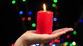 Close-up of female hand with a big red candle on bokeh background. Burning candle on a black background. Religion stock footage