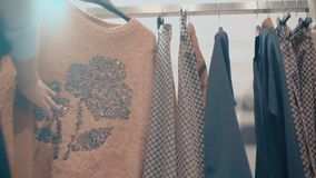 Close-up of a female hand is choosing sweatshirt in showcase stock video