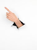 Female hand indicating a direction, paper with hole Royalty Free Stock Photos