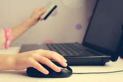Close up of female hand on computer mouse and holding a credit card. Royalty Free Stock Photos