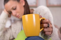 Sleepy woman holding cup of coffee royalty free stock photo