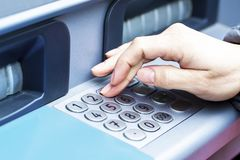 Close up of female hand entering PIN pass code on ATM bank machine keypad. Close-up of woman s hand introducing pin code at ATM machine for cash withdrawal stock images