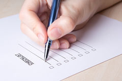 Close up of female hand filling checklist with pen. Close up of female hand filling checklist with metal pen royalty free stock photo