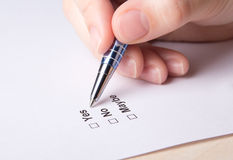 Close up of female hand filling survey with yes, no, maybe answe. Rs with pen Stock Photo