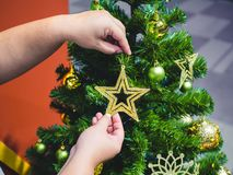 Close-up female hand hanging christmas decorative toys star gold on Christmas tree branch stock photography