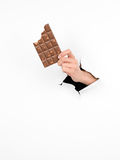 Female hand holding a bitten bar of chocolate Royalty Free Stock Images