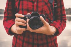 Close-up of female hand holding camera and enjoying in nature. Relax time on holiday concept travel,selective and soft focus,tone of hipster style Royalty Free Stock Images
