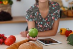 Close-up of female hand holding green apple in kitchen interiors. Many vegetables and other meal at glass table are stock photos
