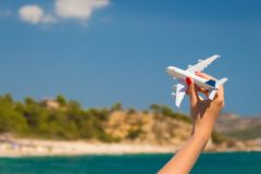 Female hand holding airplane toy at the beach stock photography