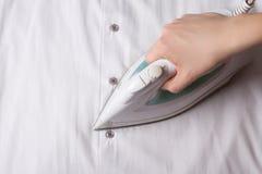 Close up of female hand with iron ironing shirt Stock Photo