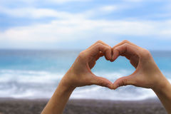 Close up of female hand making heart shape with blue sea and sky royalty free stock images