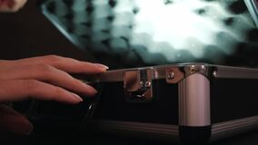 Close up of female hand opening metal briefcase. Concept. Woman opening the aluminum carrying case and lifting its lid