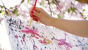 Close-up, female hand, painter, artist paints a picture of flowers in blooming spring apple orchard, she applies oil stock video