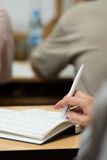 Close-up of a female hand with a pen. Royalty Free Stock Photo