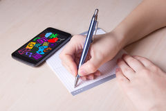 Close up of female hand with pen, notebook and phone with media Royalty Free Stock Photo