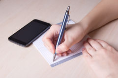 Close up of female hand with pen, notebook and phone Royalty Free Stock Images