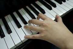close-up female hand playing grand piano. stock photo