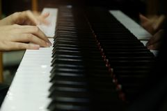 Close-up female hand playing grand piano stock image