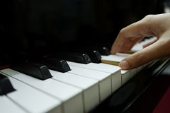 Close-up female hand playing grand piano stock photography