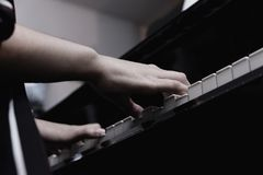 Close-up female hand playing grand piano royalty free stock image