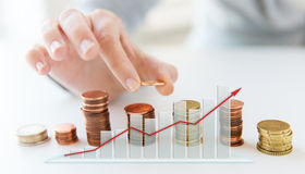 Close up of female hand putting coins into columns Stock Photos