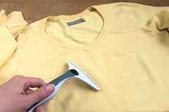 Female hands removes fuzz from yellow sweater stock photo