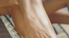 Close-up of female hand rubbing sunscreen on tanned slim leg. Unrecognizable young Caucasian woman applying suntan