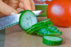 Close-up of female hand slicing fresh cucumbers Royalty Free Stock Photography