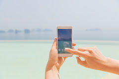 Close up of female hand with smartphone on beach Royalty Free Stock Photography