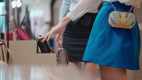 Close up. Female hand takes purses, bags and clutches from showcase stock video