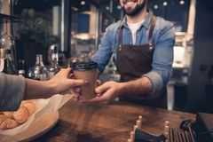 Worker giving mug of beverage to woman. Close up female hand taking cup of hot coffee from barista in confectionary shop. Purchase concept Royalty Free Stock Photos