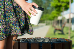 Close-up female hand throwing paper cup on trash Stock Image