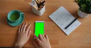 Close-up of female hand touching green chroma-key smartphone screen on table. Close-up of female hand touching green chroma-key mock-up smartphone screen on stock video