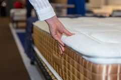 Close-up of female hand touching and testing mattress in a store. Copy space Royalty Free Stock Image
