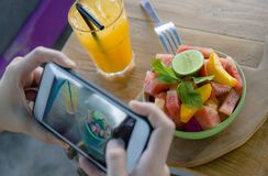 Free Close Up Female Hand With Mobile Phone Screen Taking Picture Of Fruit Salad And Orange Juice For Sharing On Internet Social Media Stock Photos - 119845323