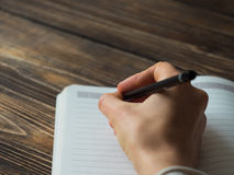 Close up of female hand writing in notepad Stock Images