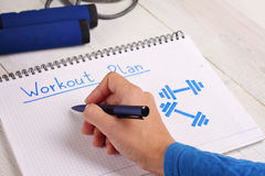 Close up on female hand writing workout plan. Woman, fitness, sport concept background Royalty Free Stock Image