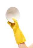 Close up of female hand in yellow protective rubber glove holding clean white bowl Stock Images