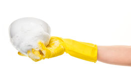 Close up of female hand in yellow protective rubber glove holding clean white bowl in foam Stock Images