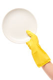 Close up of female hand in yellow protective rubber glove holding clean white plate against white Royalty Free Stock Photos