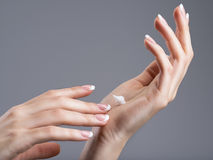 Close-up female hands apllying hand cream Stock Photos