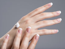 Close-up female hands apllying hand cream Stock Photo