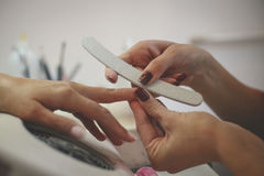Close-up of female hands being manicured. Royalty Free Stock Photography