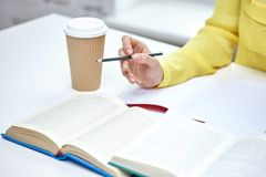 Close up of female hands with books and coffee Stock Photo