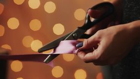 Close-up of female hands, cut the ribbon for the manufacture of handmade gift for Christmas to your loved ones. On the. Background of blurred lights garlands stock footage