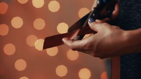 Close-up of female hands, cut the ribbon for the manufacture of handmade gift for Christmas to your loved ones. On the. Background of blurred lights garlands stock video footage